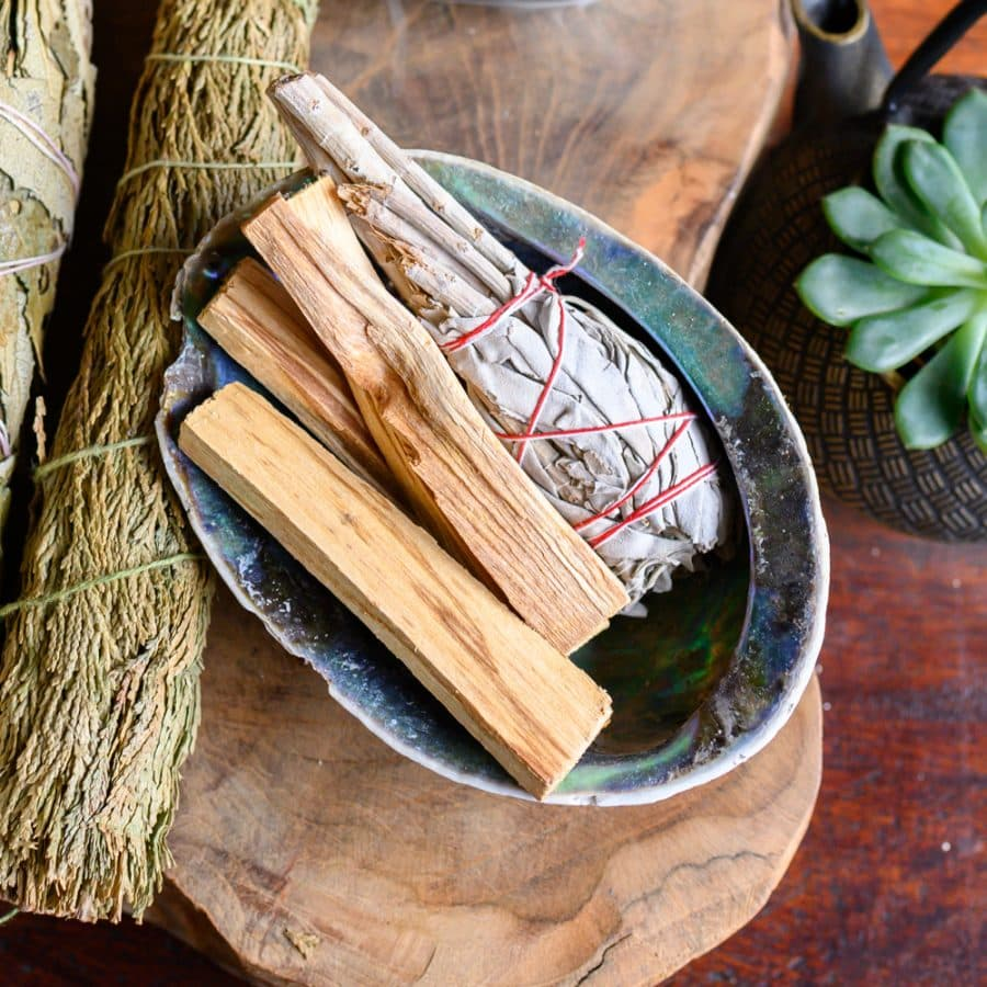Smudge Sticks Weißer Salbei mit Palo Santo in Abalonemuschel auf Holz mit Kräutern