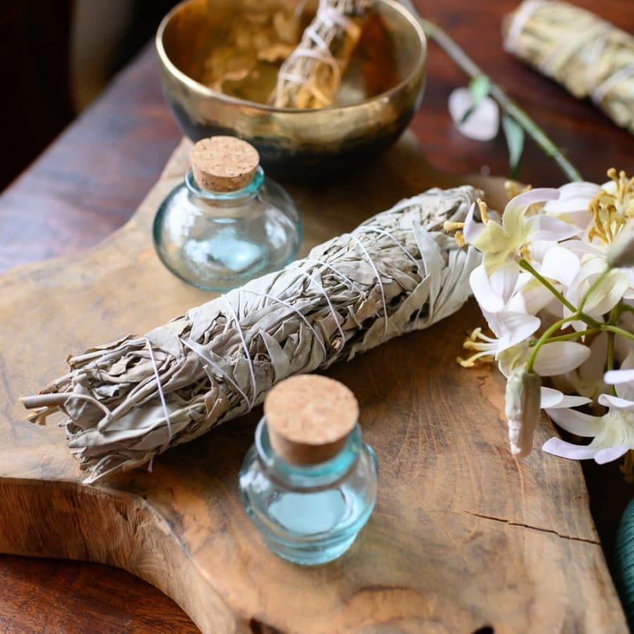 smudge stick weißer Salbei mit glasfläschchen auf Holz mit Blumen