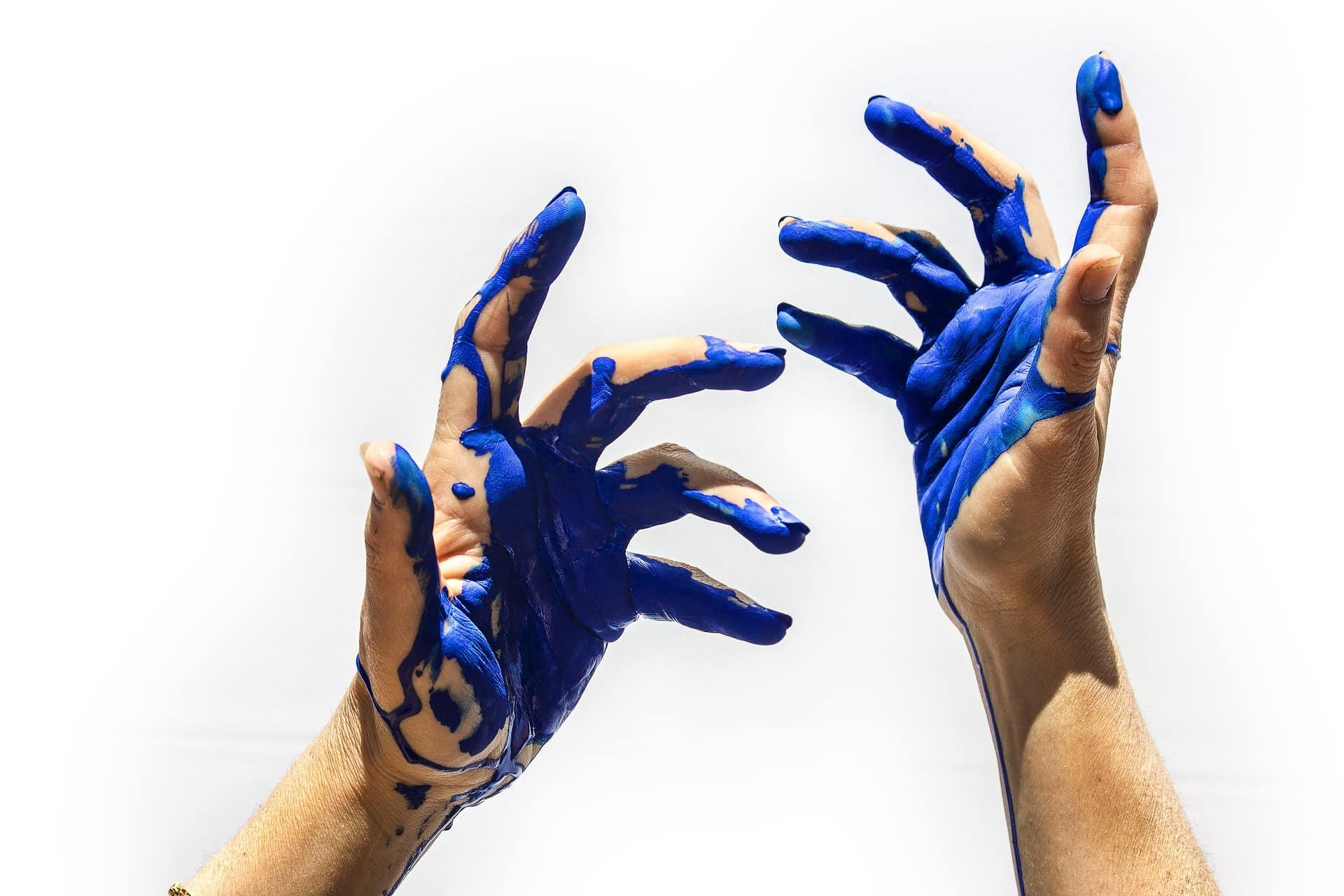 zwei Hände beschmiert mit blauer Farbe vor weißer Wand