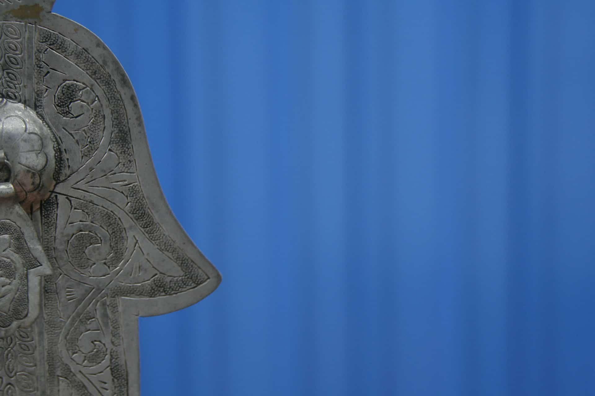 Hamsa Hand aus Metall Ausschnitt vor blauem Hintergrund