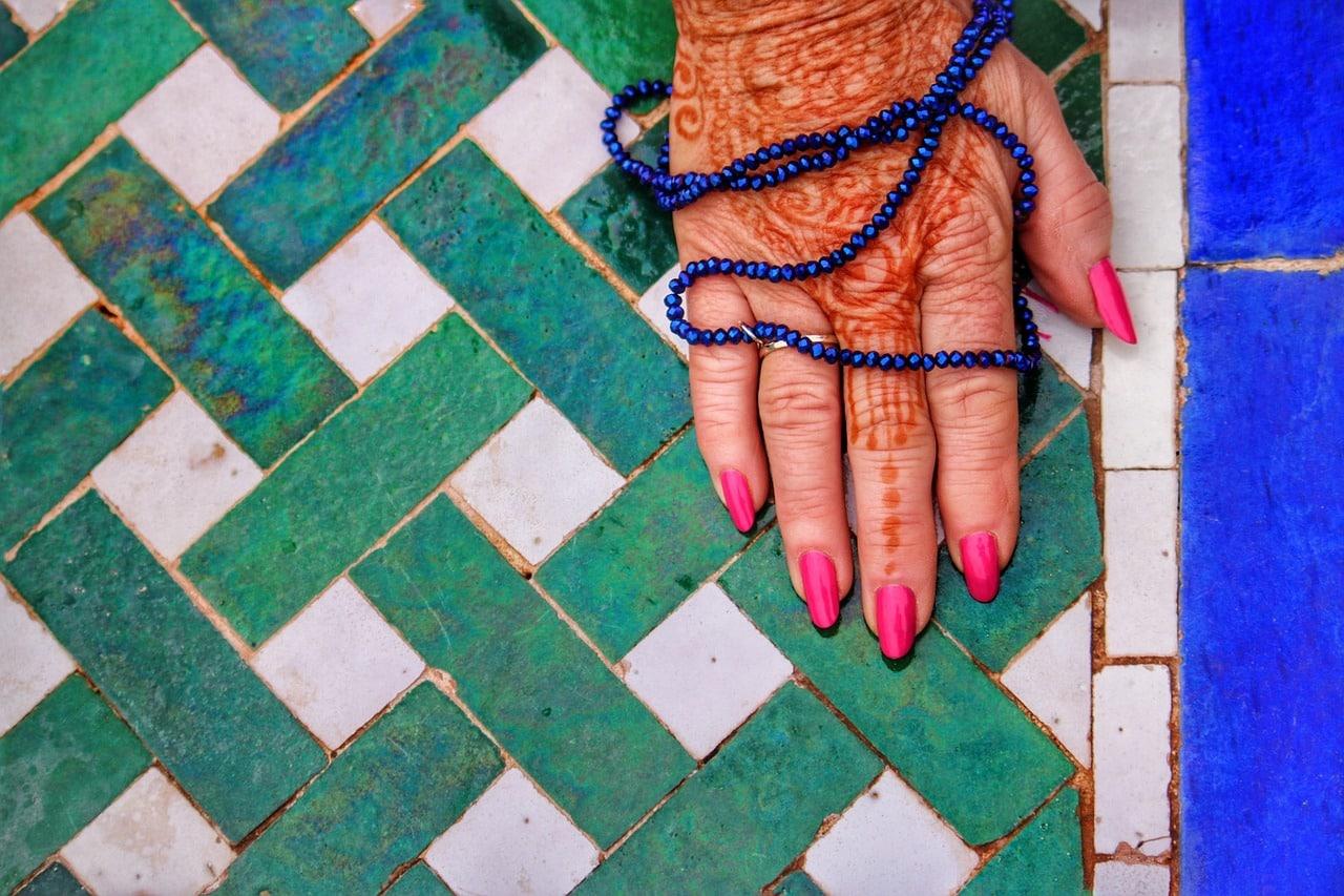 Hand mit Henna und Blauer Perlenkette auf Fliesen mit grünem und weißem Flechtmuster und Blau
