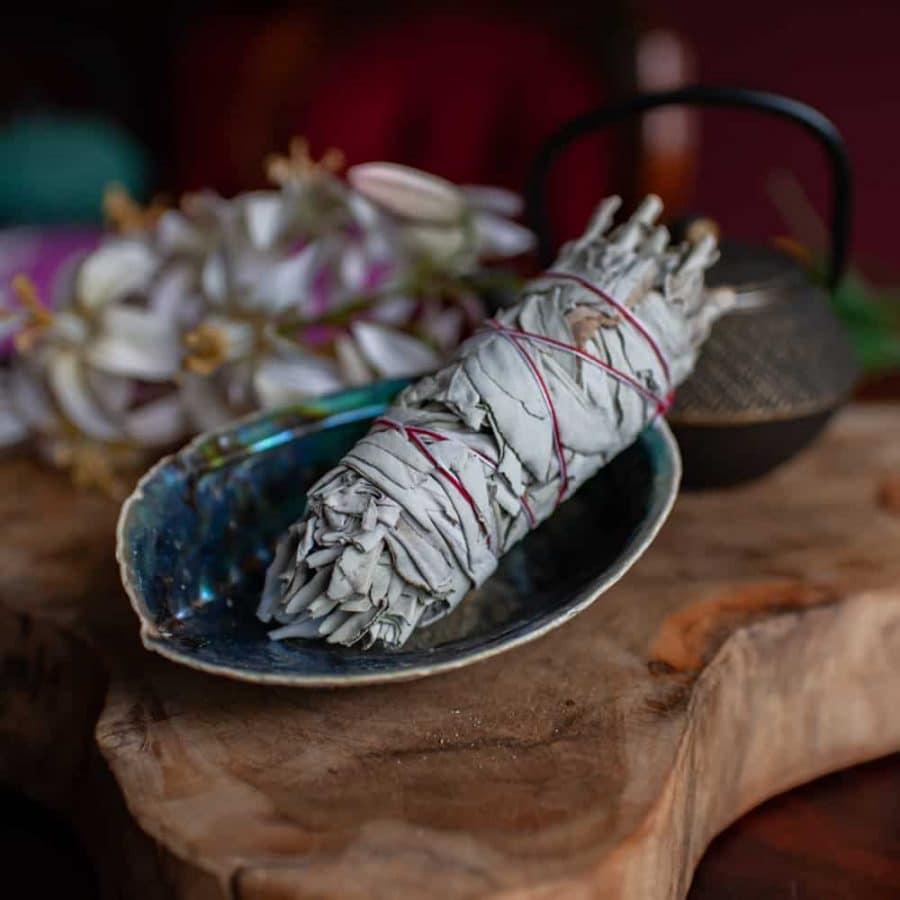 Smudge-Stick Weißer Salbei in blau schimmernder Abalonemuschel auf Holz mit Blumen und Teepott im Hintergrund