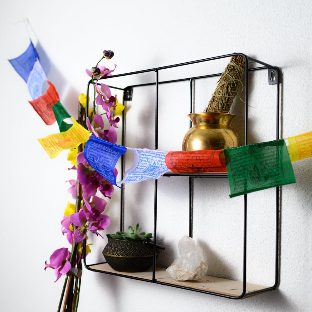 bunte Fahnen vor Metallregal mit spiritueller Deko und Blumen vor weißer Wand