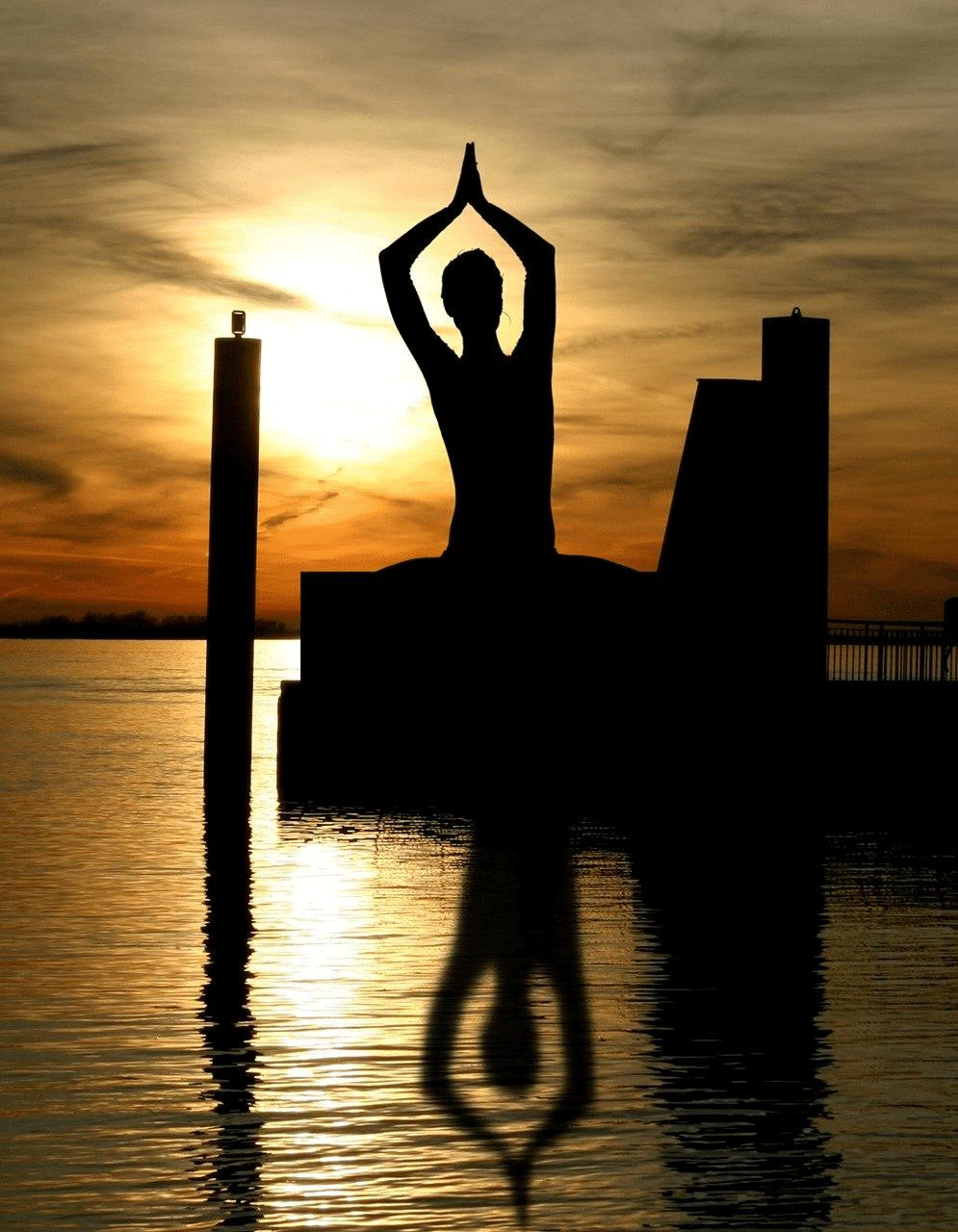 silhouette Frau yoga übung am Wasser vor Sonnenuntergang schatten