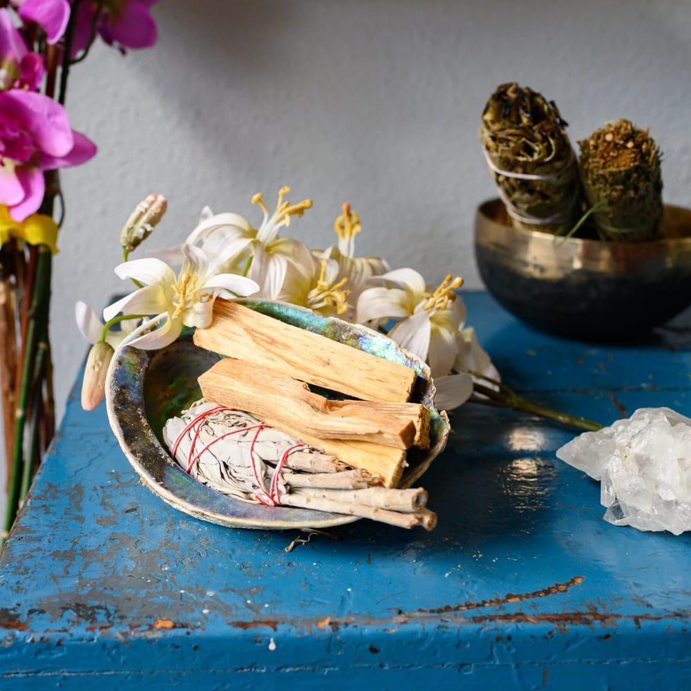 Smudge und Palo Santo Holz in Schale auf blauem Tisch mit Blumen und Kristall
