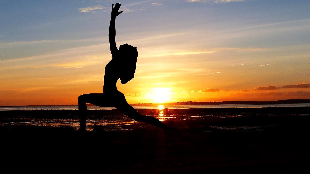 Yoga position Yogaübung Silhouette Frau am Strand vor Sonnenuntergang