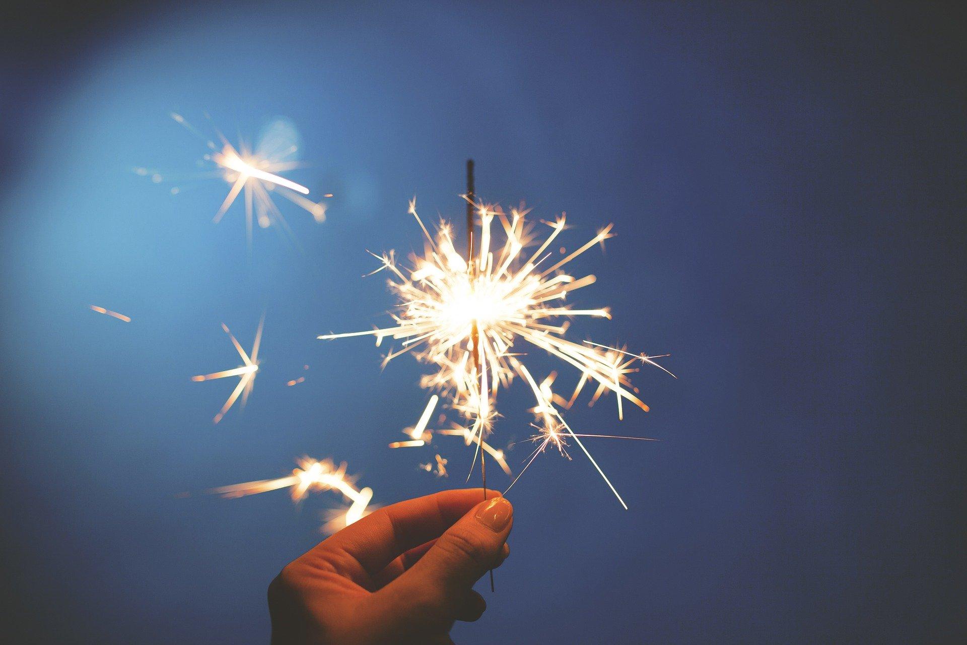 Hand hält brennende Wunderkerze Funken auf blauem Hintergrund