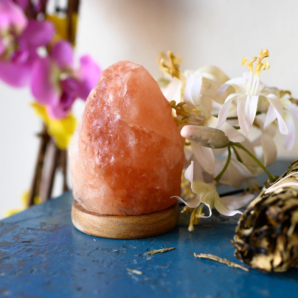 Himalaya Salzkristalllampe mit Holzfuß auf blauem Tisch mit Blumen