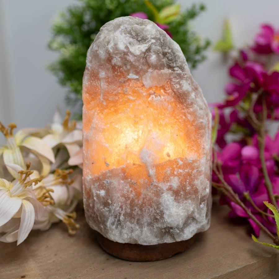 Himalaya Salzkristalllampe leuchtend auf Tisch mit Blumen