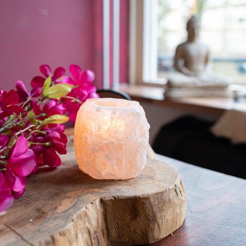 Salzlampe Salzteelichhalter auf Holzscheibe mit pinken Blumen Buddhastatue im Hintergrund