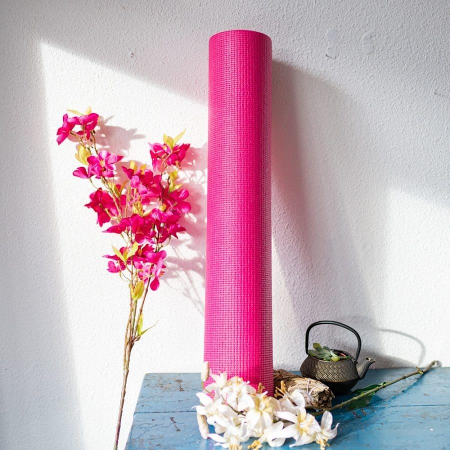Pinke Yogamatte an weiße Wand gelehnt mit Blumen