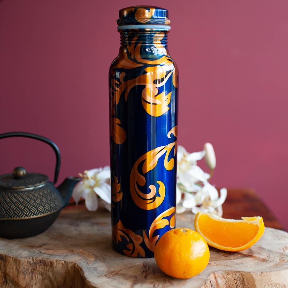Blaue Kupferflasche mit floralem Design vor roter Wand auf Holz mit Orangen und Teepot