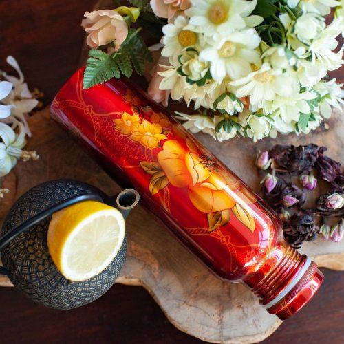 Rote Kupferflasche mit Blumenmuster auf Holz umgeben von Blumen und Teepott mit Zitrone