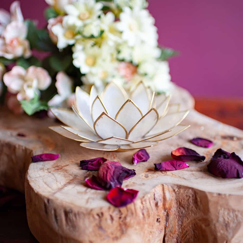 Lotusblume Bedeutung Lotusblume Stimmungslicht Teelichthalter weiß und gold auf Holz mit Blüten