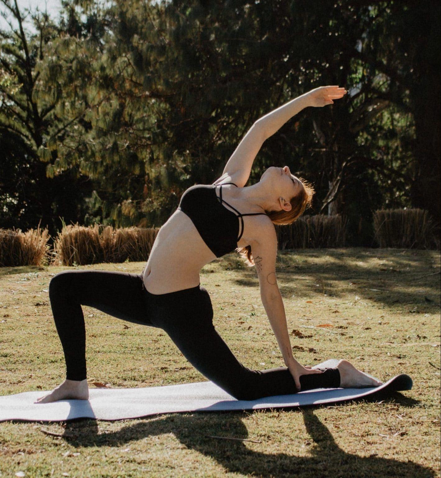 Yoga Frau macht Yoga in Natur mit Sonne auf Yogamatte