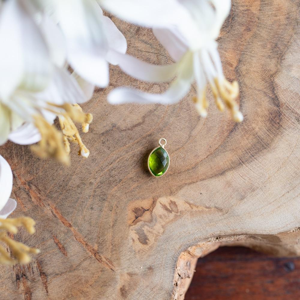 Geburtsstein August Peridot Anhänger mit Gold auf Holztisch mit Blumen