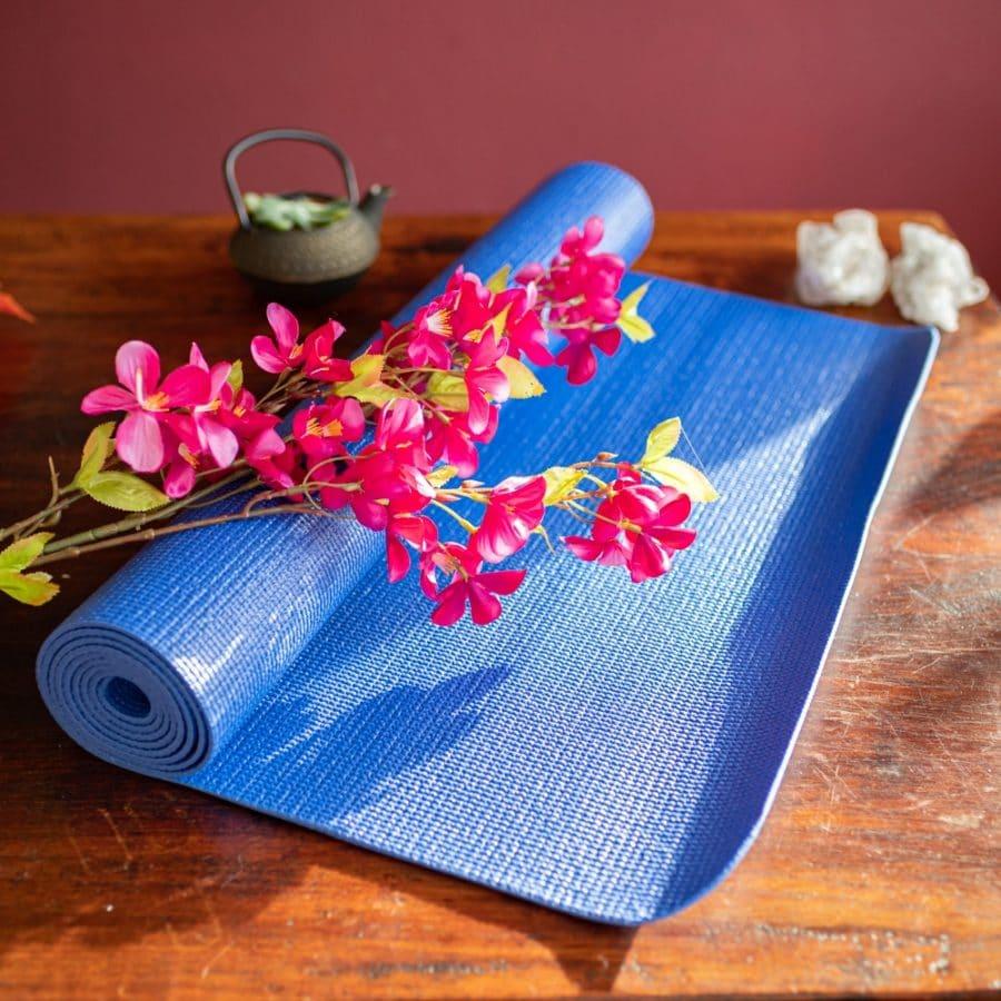 Blaue Yogamatte auf Holztisch vor roter Wand mit Blumen