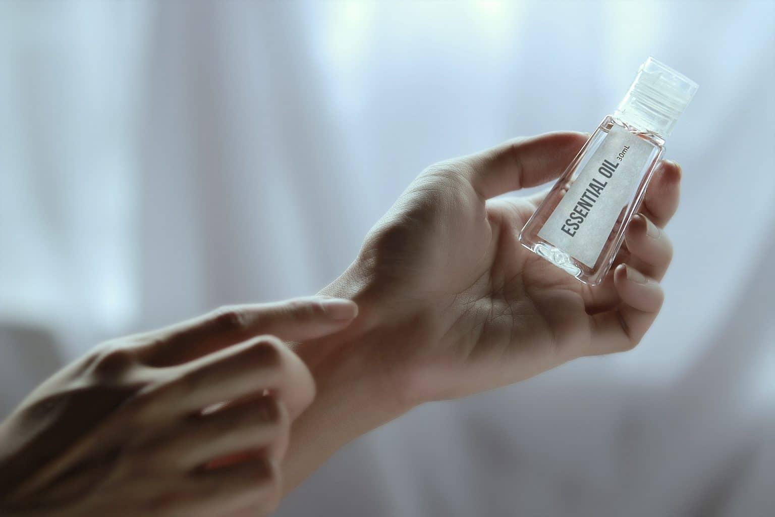 Hände halten Essential Öl vor weißem Vorhang
