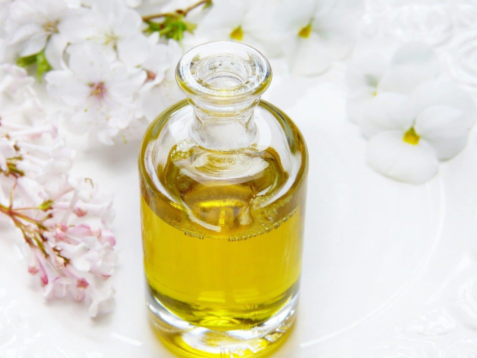 gelbliches Duftöl in Flasche mit weißen Blumen