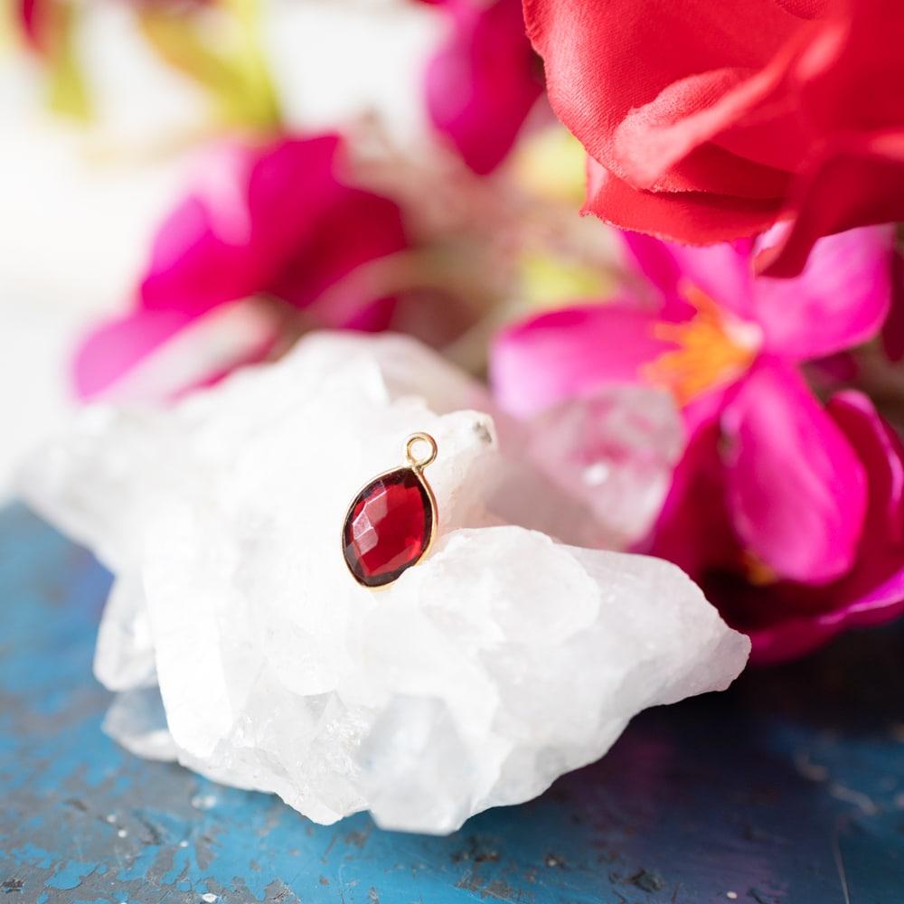 Geburtsstein Roter Granat auf kristall mit Blumen