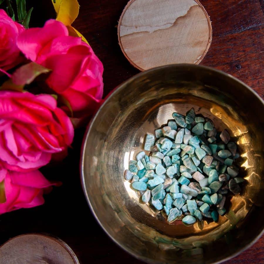 Geburtsstein März Aquamarin Steine in goldener Klangschale auf Holztisch mit Blumen