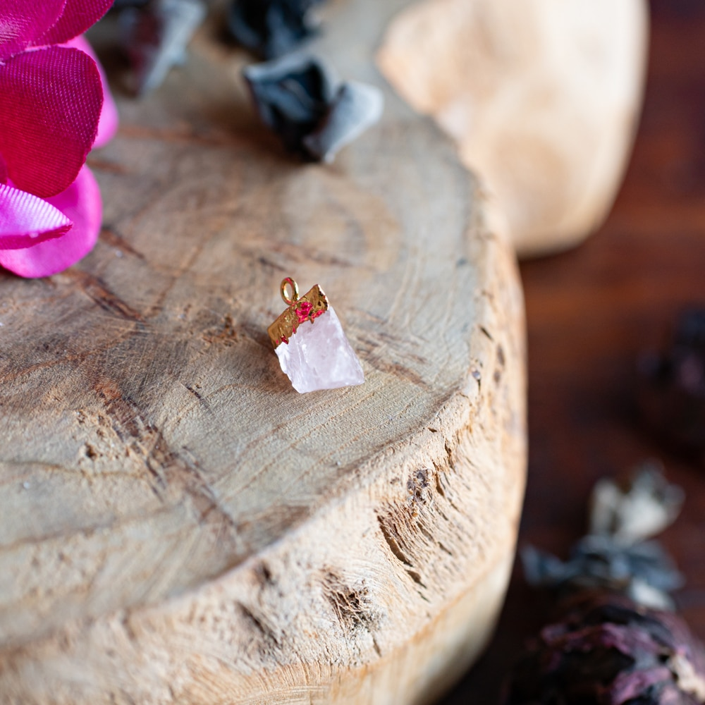 Geburtsstein Oktober Rosenquarz Anhänger mit Gold auf Holz mit Blumen