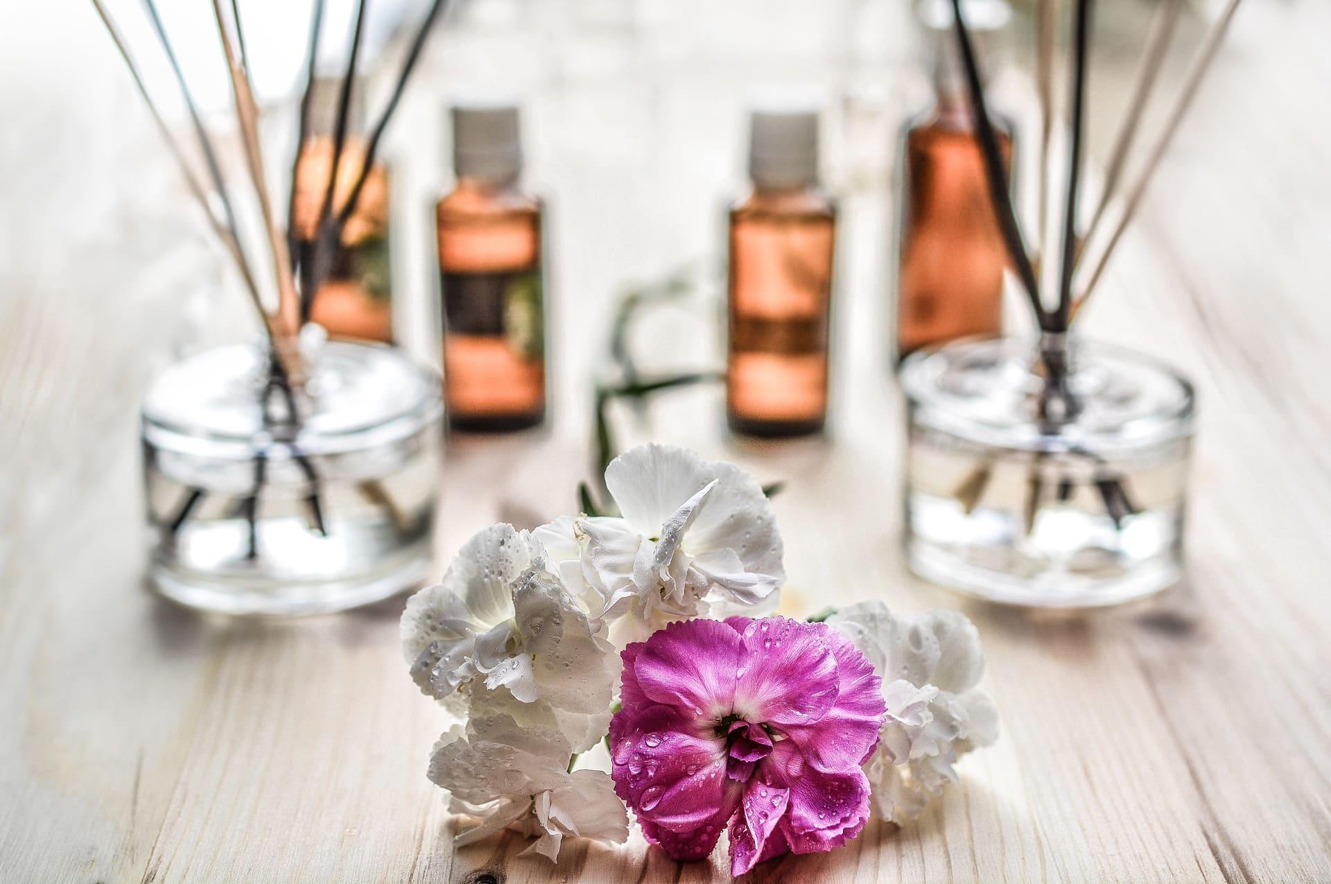 Duftstäbchen im Hintergrund hinter Blumen mit Duftöl