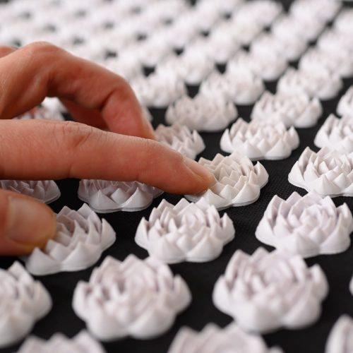 Finger streichen über Spiru Nagelmatte Schwarz Nagelmatte mit weißen Blumen Spitzen auf weißem Hintergrund