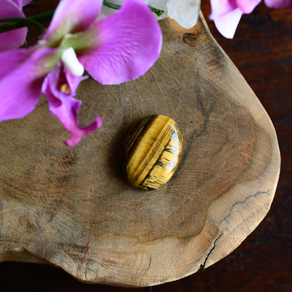 Tigerauge Edelstein auf Holz mit Blumen Sternzeichen Jungfrau