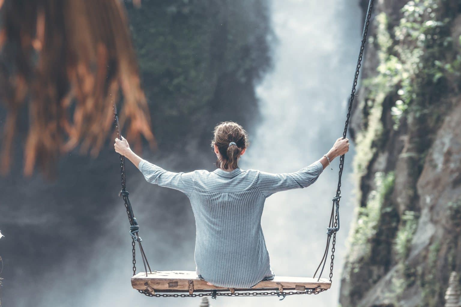 Frau mit gestreifter Bluse auf Schaukel vor Felsen und Wasserfall