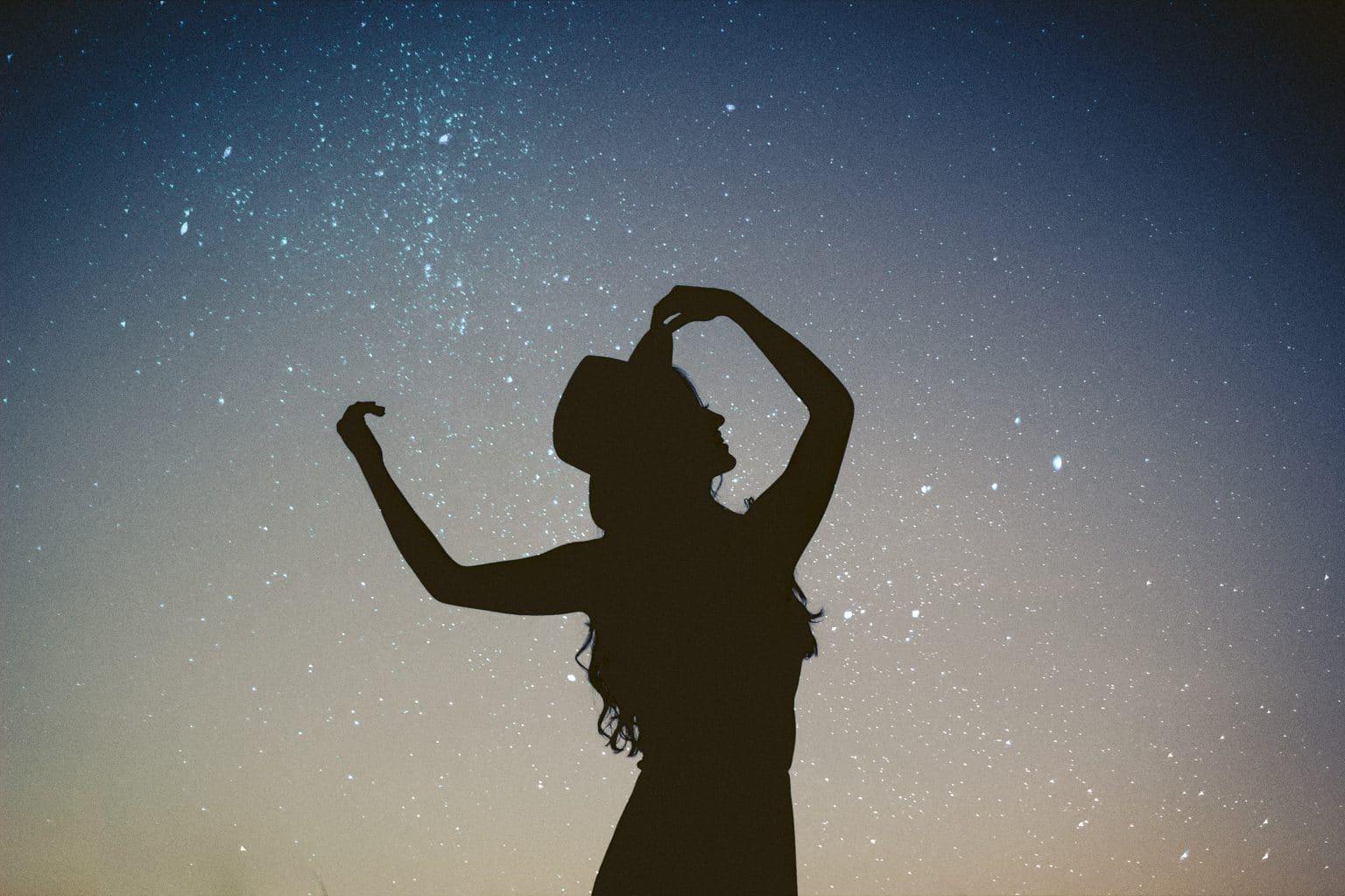 Sternzeichen Löwe Frau mit Hut Silhouette vor Sternenhimmel