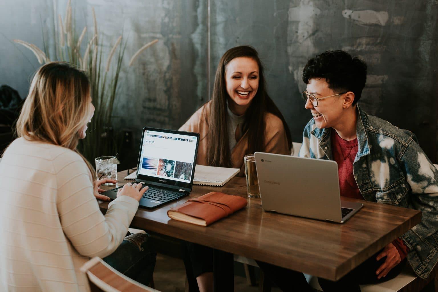 drei Leute an Holztisch mit Laptops und Notizbüchern lachen