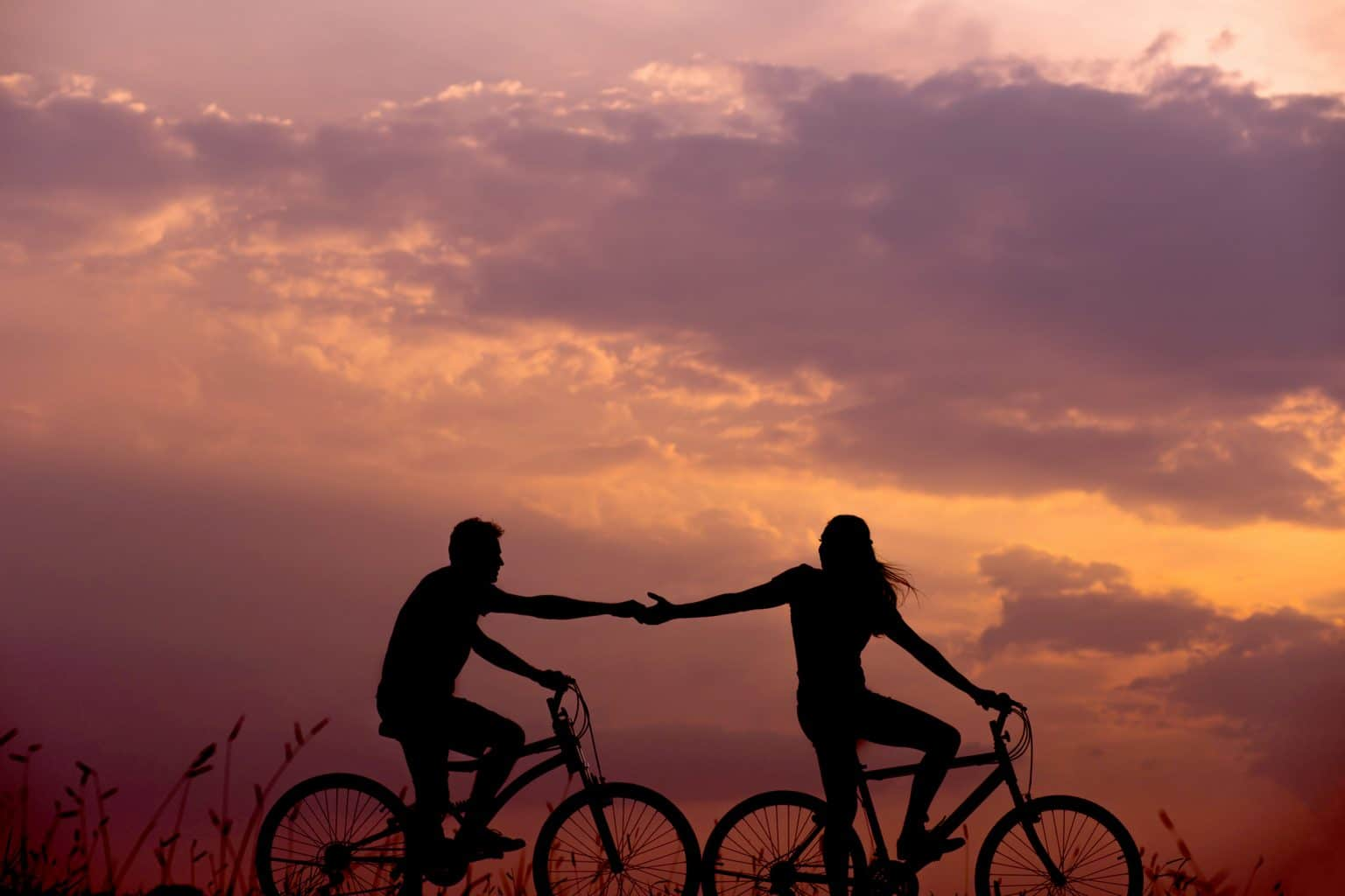 Silhouette Paar auf Fahrrädern in Feld vor orange violettem Himmel