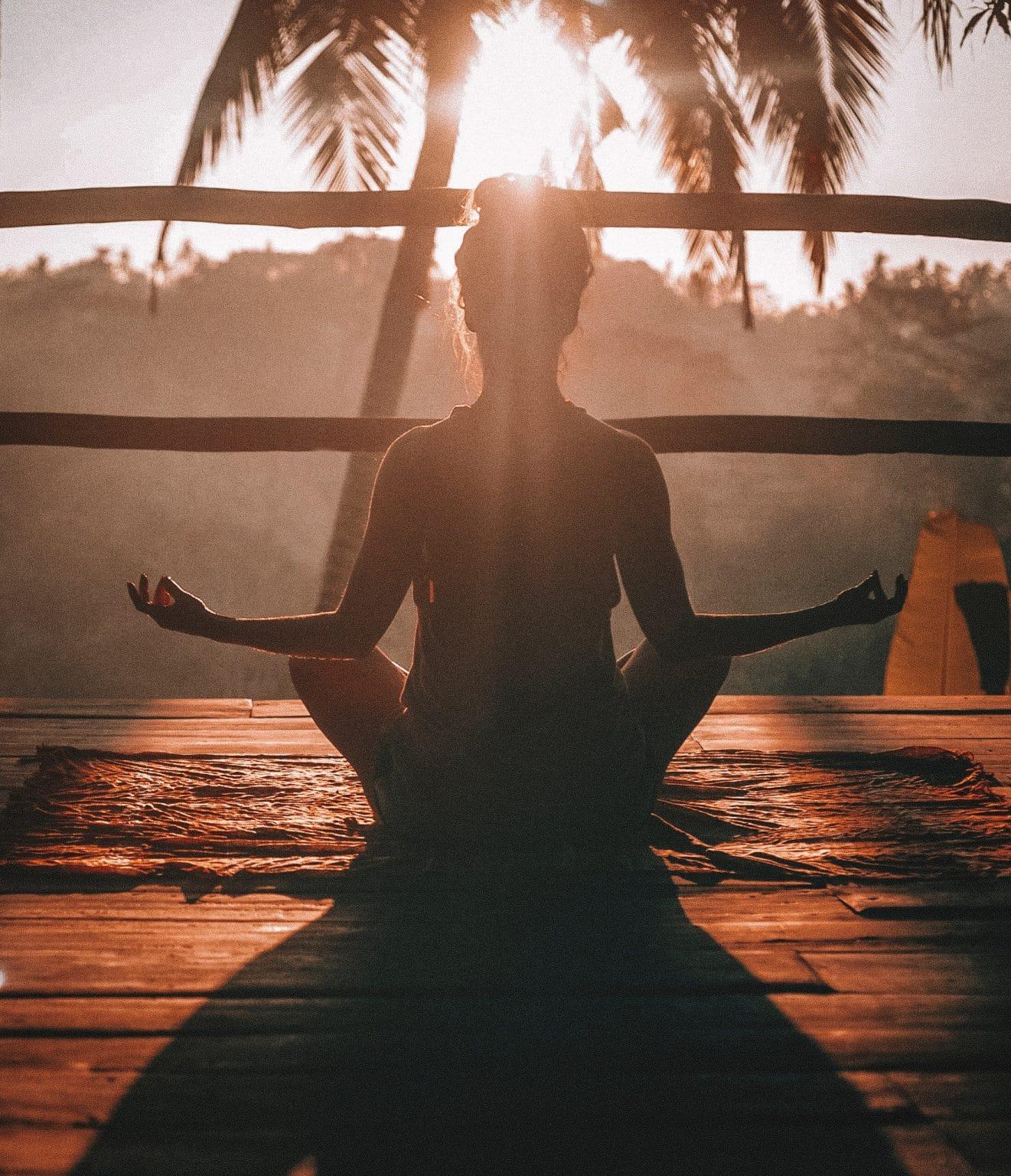 Frau in Yogasitz auf Holzterasse vor Palme