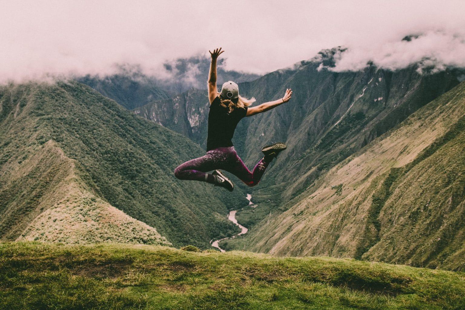 Sternzeichen Zwilling Sportive Frau springt vor grüner Berglandschaft