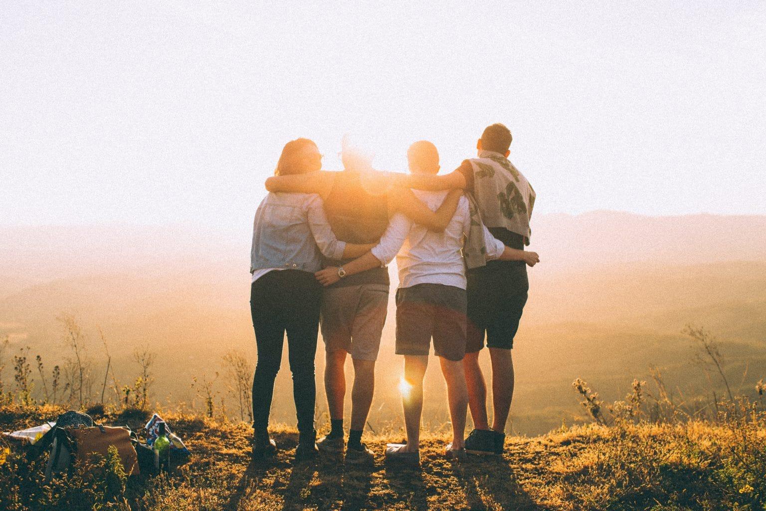 Sternzeichen Waage vier Freunde umarmen sich in Natur vor Sonnenuntergang