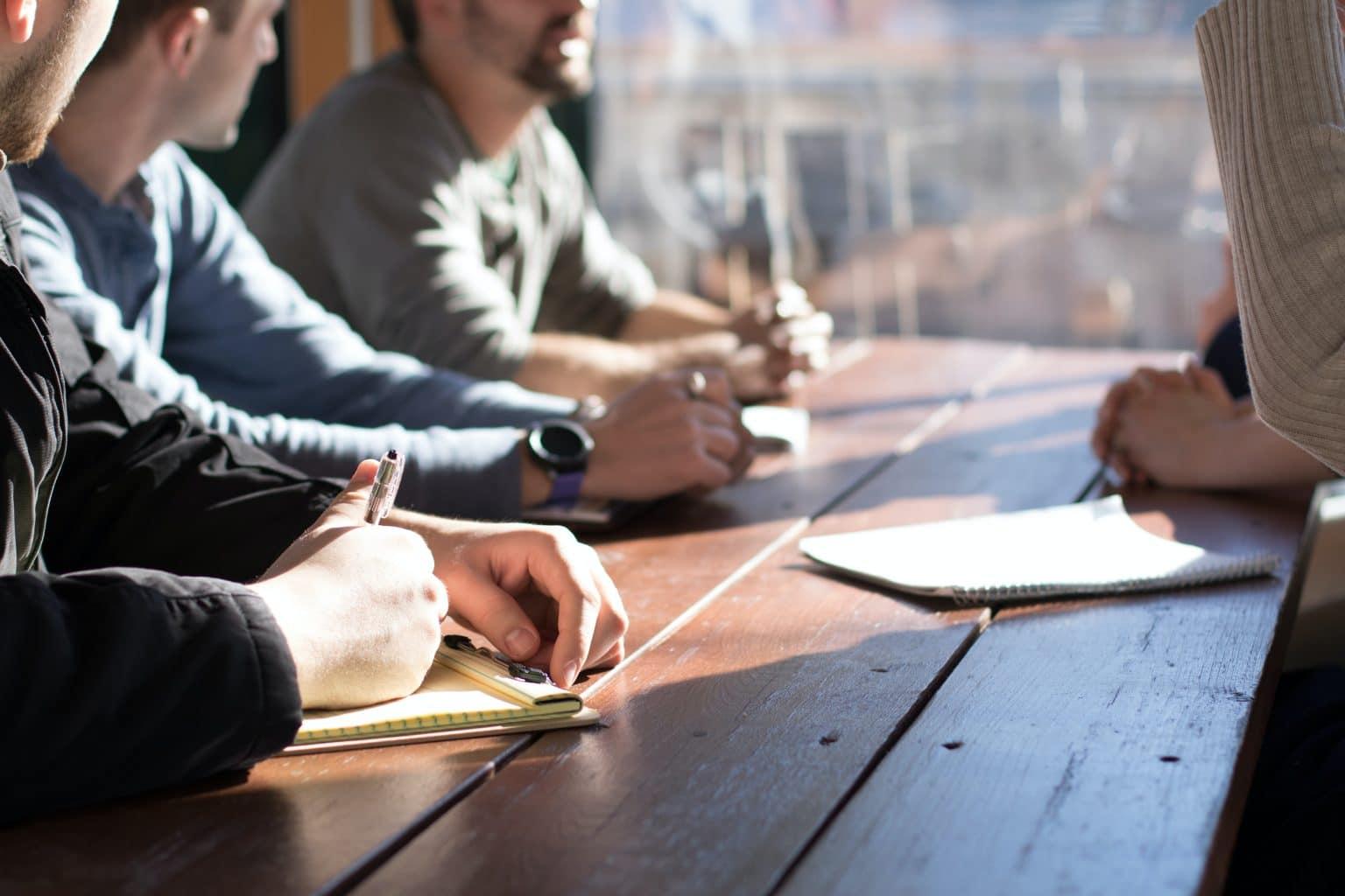 Sternzeichen Waage Leute meeting an Holztisch mit Notizbüchern