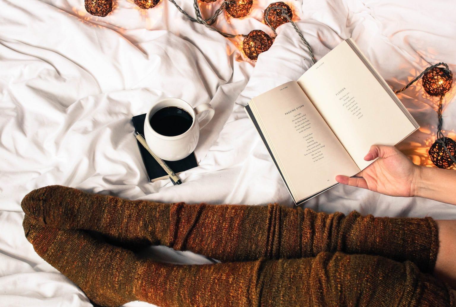 Beine mit hohen braunen Socken mit Buch und Kaffee auf weißer Bettdecke mit Lichterkette