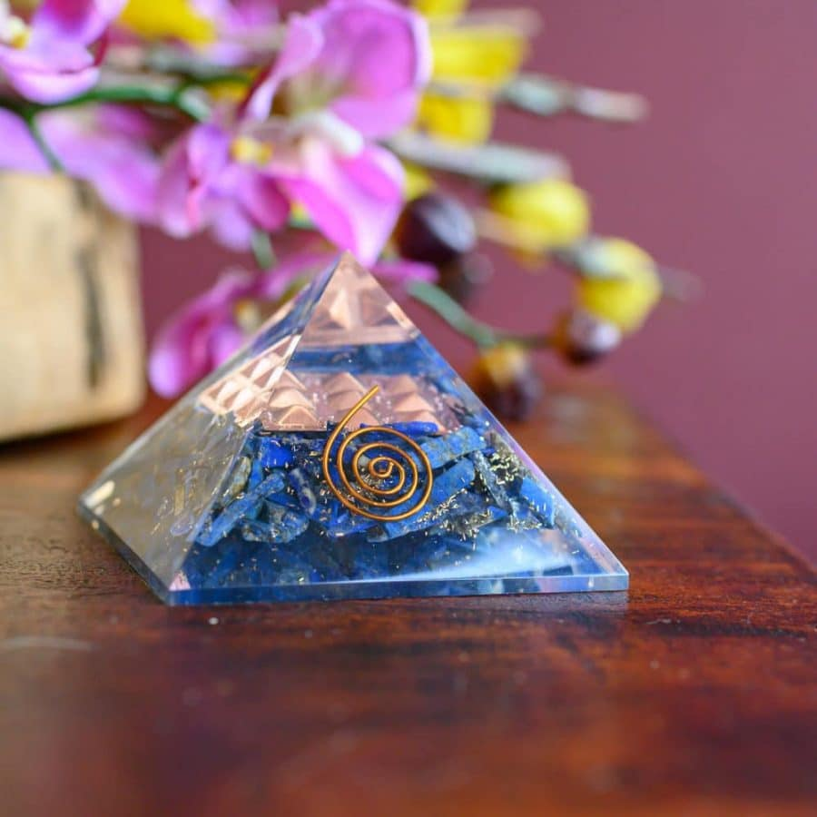 blaue Kristallpyramide mit goldener Spirale auf Holztisch mit Blumen vor weinroter Wand