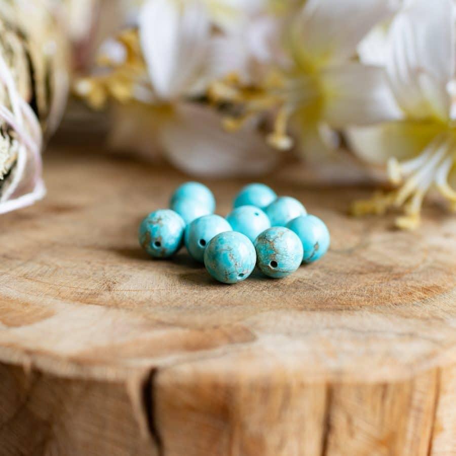Entstehung Edelsteine Türkis Perlen auf Holz vor weißen Blumen