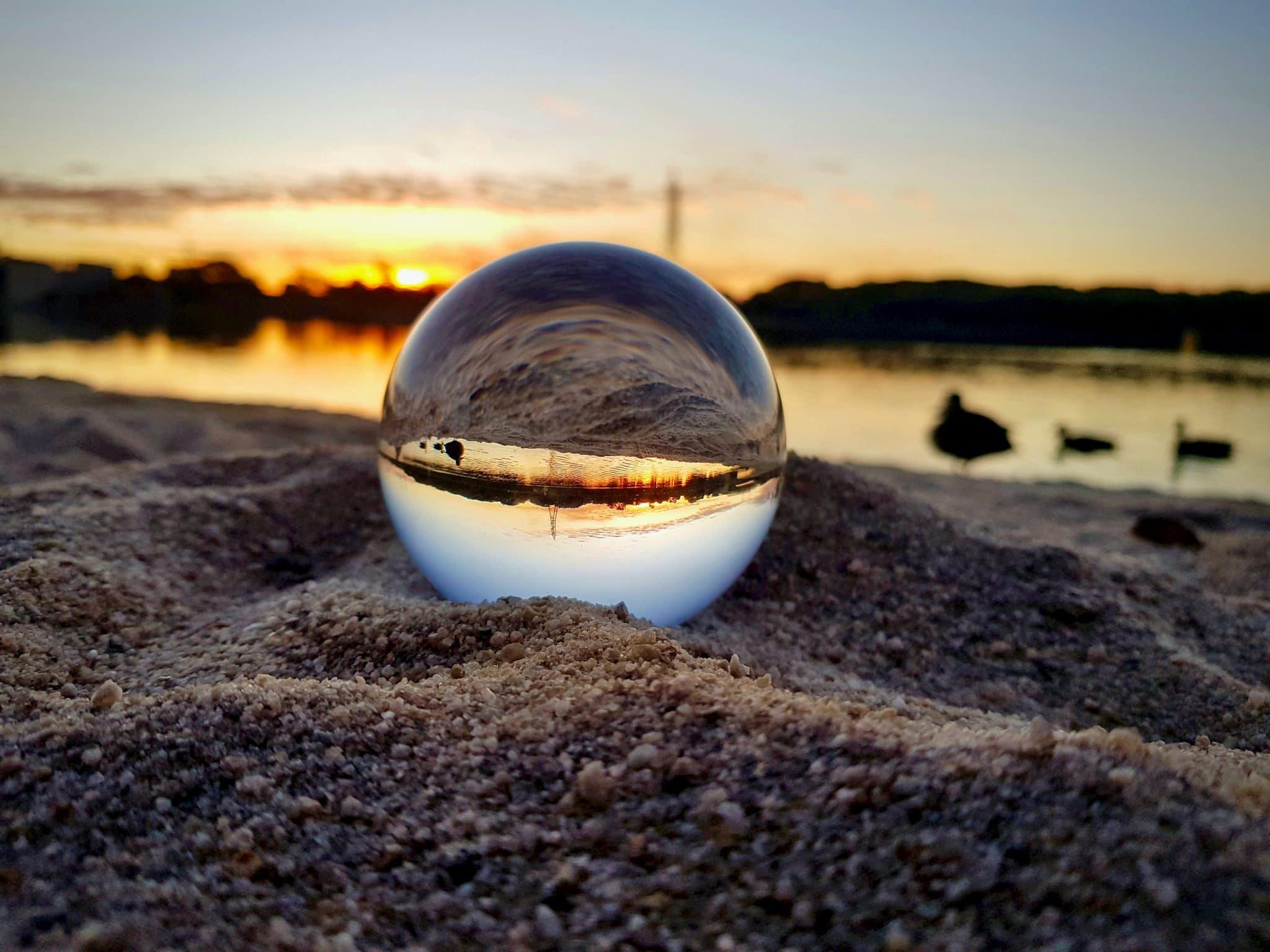 Glaskugel Fotografie Glaskugel im Sand vor see und sonnenuntergang