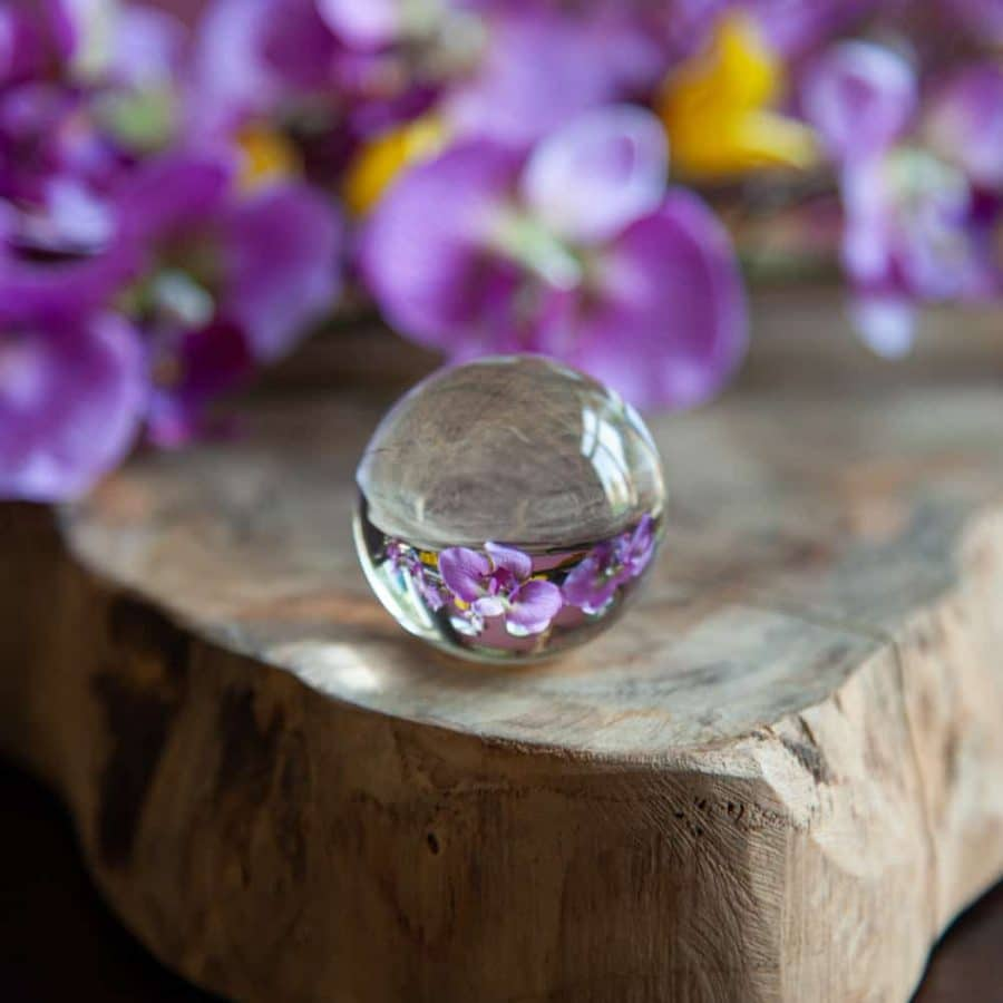 Glaskugel Fotografie Kristallkugel auf Holz mit lila Blumen im Hintergrund