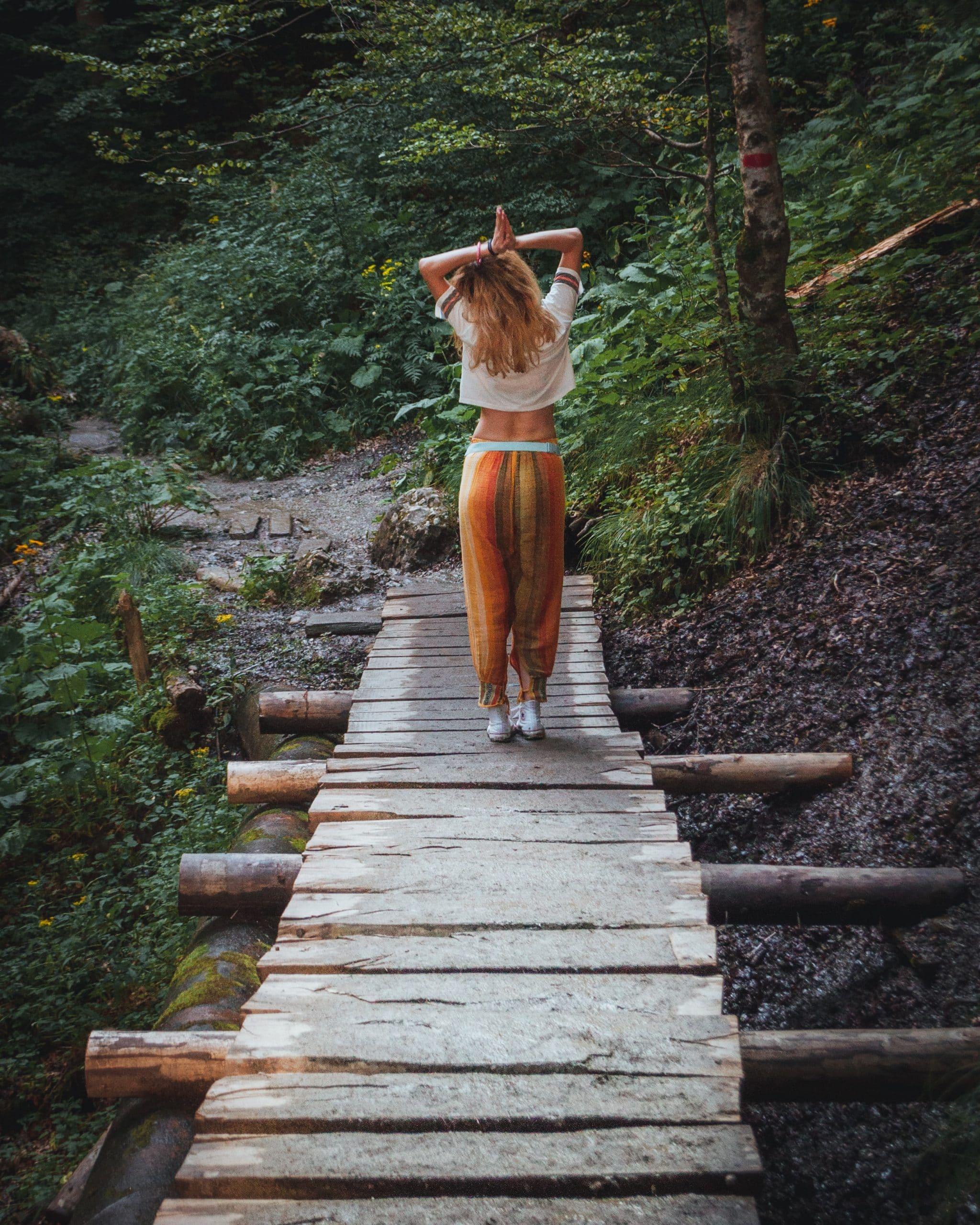 Frau in Bohemian Kleidung auf Holzbrücke im Dschungel