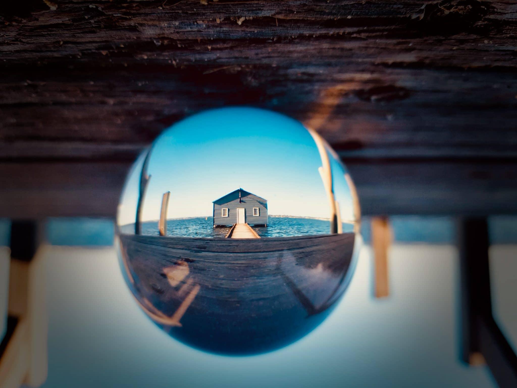 Glaskugel Fotografie Haus am See durch Glaskugel Hintergrund auf dem Kopf