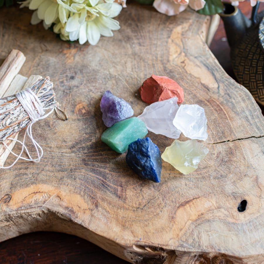 Chakra Steine auf Holz mit Blumen und Salbei