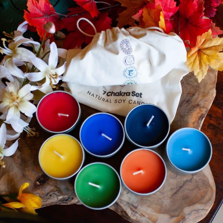 Bunte Chakrakerzen set mit beutel auf Holz mit Blumen