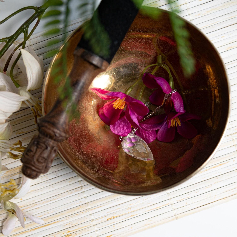 Klangschale mit Anstereicher und Blumen und Pendel