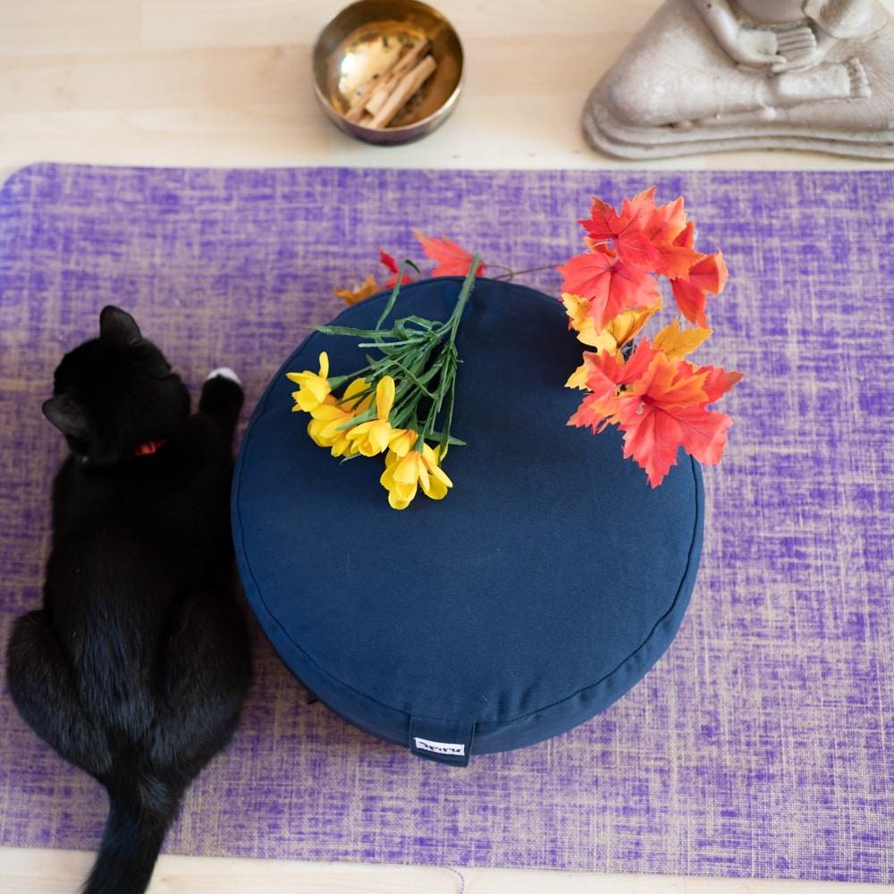 Ashtanga yoga bolster kissen blau auf Lila matte mit Blumen und Katze