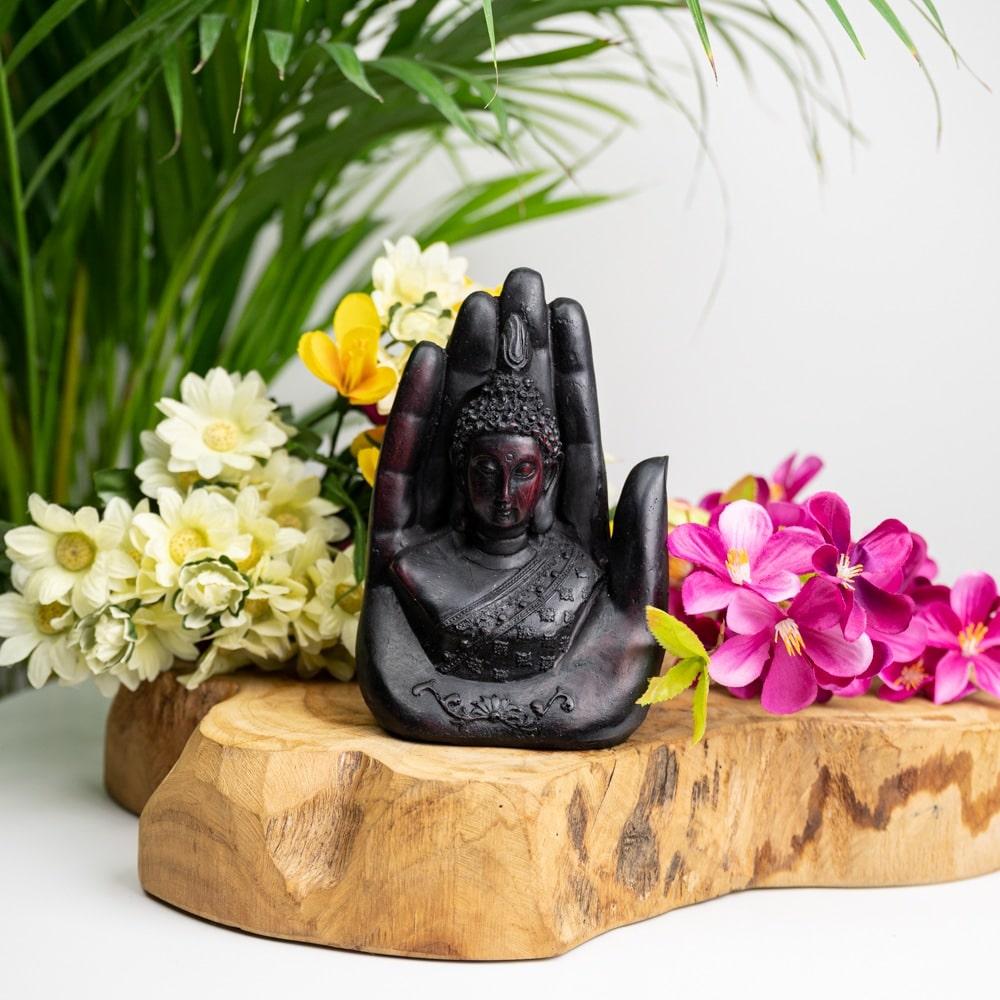 Buddha in Hand schwarz Statue auf Holzscheibe mit gelben und rosa Blumen