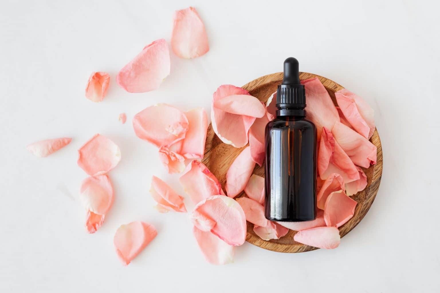 Massageöl pipetten flasche mit rosenblüten auf Holzteller